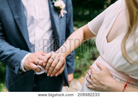 Bride and groom showing wedding rings. Outdoors. Artwork. Soft focus