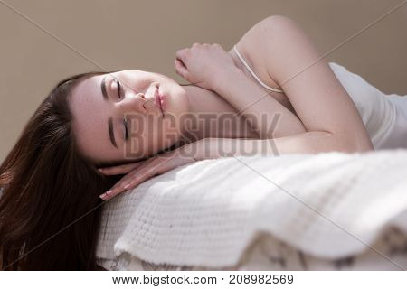 Caucasion girl get comfort and satisfaction lying on bed in the light room at home. Sunny morning with happy smile