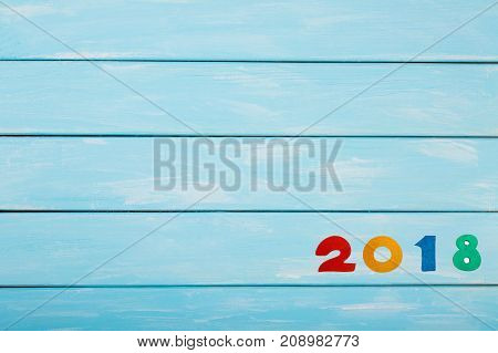 Happy New Year 2018 of real wooden figures on pastel blue wooden background. Nice template for your christmas or New Year Project