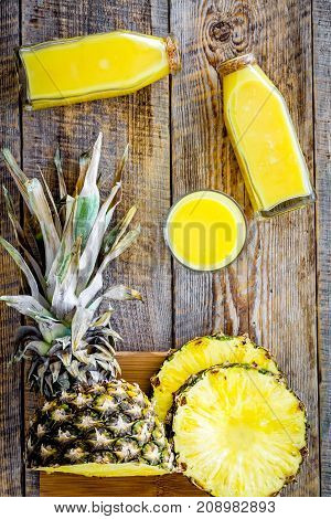 Freshly squeezed pineapple juice near fruit slices on wooden background top view.