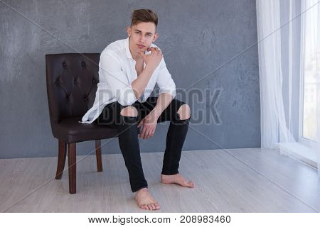 Serious successful man advertising fashion look on chair photoshoot concept. Gorgeous outfit lifestyle