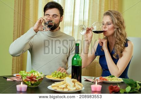 Couple drinking wine at table. Young man and woman indoors. Toasts about love.