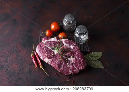 Raw steak with spices and ingredients for cooking. Top view