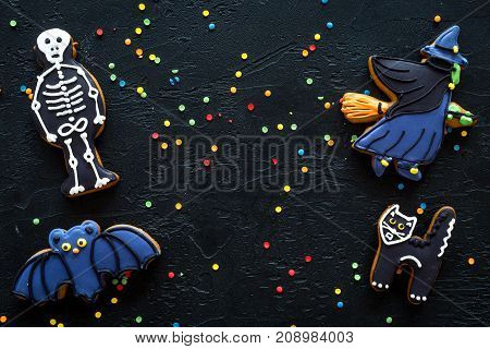 Bright halloween gingerbread cookies on black background top view.
