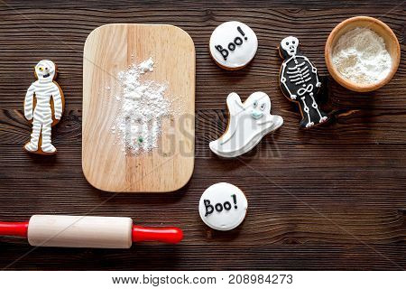Cook halloween gingerbread cookies in shape of skeleton, ghost. Sweets near desk and rolling pin. wooden background top view.