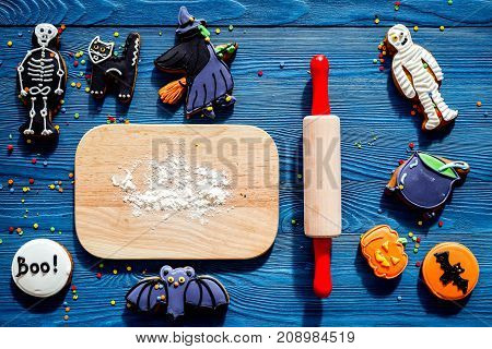 Cook halloween gingerbread cookies in shape of skeleton, mummy. Sweets near desk and rolling pin. blue wooden background top view.