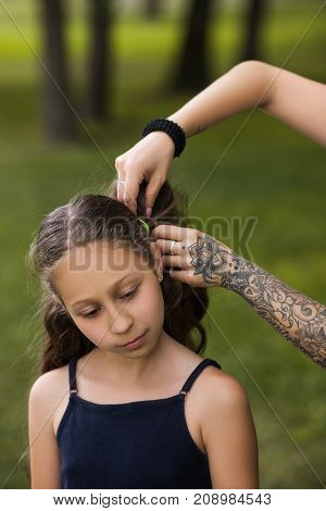 Teenage hairstyle. Modern beauty youth activity. Pretty young girl in focus on foreground. Active life, mother care background. Stylish child