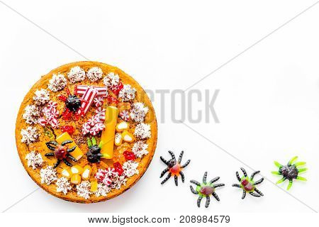 Gummy spiders crawls toward pie for halloween on white background top view.