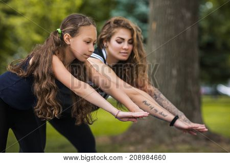 Healthy lifestyle. Active gymnastics together. Yoga exercise outdoors, female health beauty, teenage sport with coach. Nature background, entertainment outside