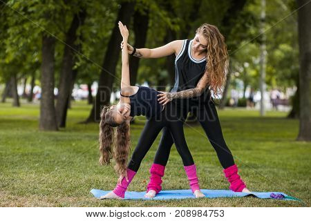 Teenage sport outdoors. Teamwork gymnastics. Yoga training exercise with coach, healthy beauty. Nature background, creative entertainment outside