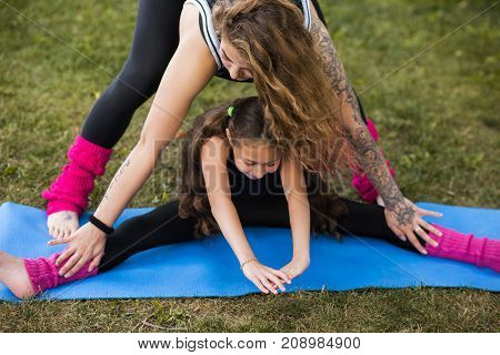 Active teenage sport. Family exercise for stretching. Teamwork gymnastics with coach, healthy beautiful lifestyle. Nature background, creative and fun entertainment outdoors