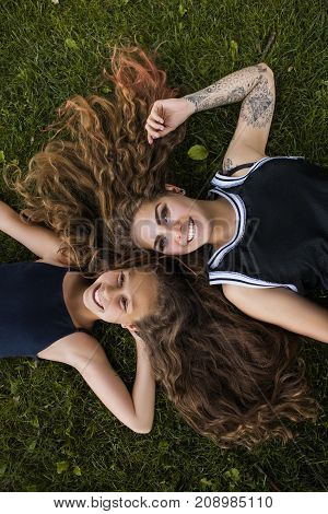 Natural beauty. Happy summer life. Young smiling girls in park top view, nature background. Beautiful hairstyle, happiness together, relaxed dreaming mood
