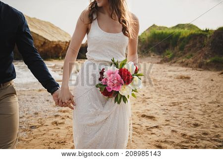 Outdoor beach wedding ceremony near the ocean, close up of hands of stylish couple with wedding bouquet, bride is holding her man.