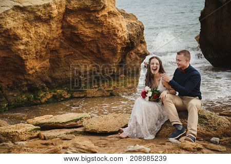 Outdoor beach wedding ceremony near the sea, stylish happy smiling groom and bride are sitting on stones, having fun and laughing.
