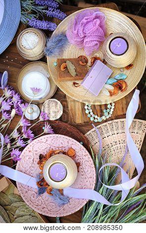 Flat lay spa accessories, handmade artisan soap, fresh flowers, wisp of bast, candles, bath salt etc.