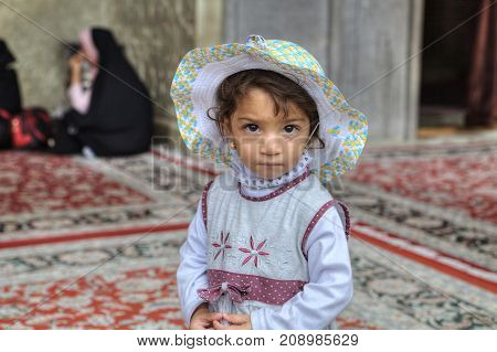Fars Province Shiraz Iran - 19 april 2017: Shah Cheragh Shrine Close-up portrait of an unknown Iranian girl about four years old standing in the courtyard of the mosque.