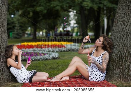 Fun activity on nature. Forever young. Stylish girls with soap bubbles, park background. Happy summer life, creative family picnic
