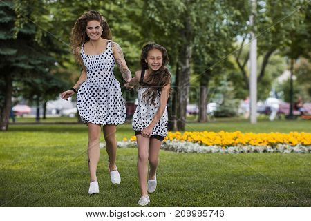 Leisure time in park. Happy summer life. Family fun, stylish youth lifestyle, nature background. Forever young, funny and beautiful running girls