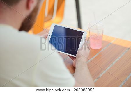Tablet In The Hands Of A Man Who Sits At A Table With A Glass Of Drink