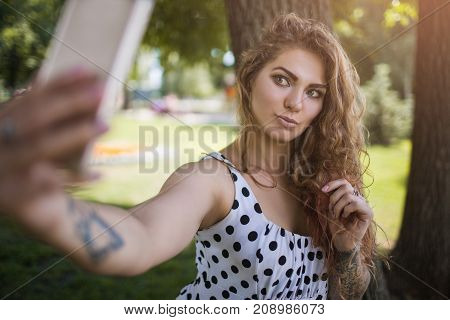Hipster behavior. Modern youth style. Trendy social media selfie, park background. Summer lifestyle, beautiful and stylish girl with mobile phone