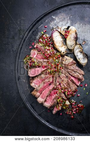 Barbecue dry aged caveman wagyu porterhouse steak with onion and pomegranate salsa as top view on a board with copy space on left