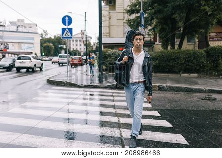 urban fashion confident rock style man walking with guitar. Music lifestyle city life concept