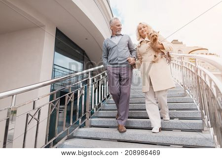 An elderly couple is walking. They go down the stairs. A woman has a dog in her arms. They smile and look at each other.