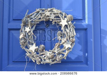 Christmas silver wreath hanging on the blue door. Original New Year Christmas decorations.
