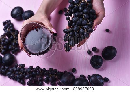 composition of wine, grape and plums on a pink background
