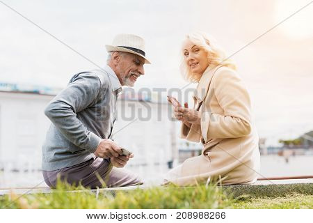 An elderly couple is sitting on the edge of a flower bed. They are looking at something on each other's smartphones. They are having fun