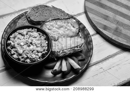 Baked potatoes with mushrooms and vegetables on a plate black and white poster