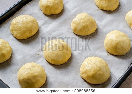 Yeast buns before baking lie on baking sheet with baking paper. Round buns are smeared with egg. Cooking process
