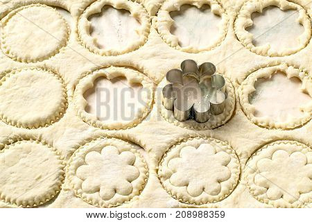 From rolled out dough cut figured cookies with help of metal cutter. Culinary background of dough with patterns in form of circles and flowers