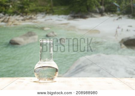 Clean water in a glass laboratory flask on wooden table on sea background. Ecological concept, the protection of water resources, the test of purity and quality of water.