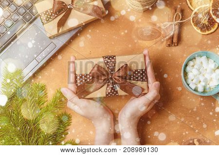 Top view Happy new year festival or Birthday and Merry Christmas day background concept. Hands holding the little present. Object on the modern brown rustic wood at home office desk