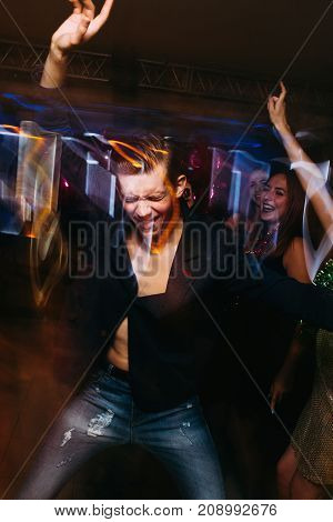 Active dancing male on dance floor in motion. Joyful New Year in night club, positive Christmas celebration. Disco party in blurred colors, modern youth life