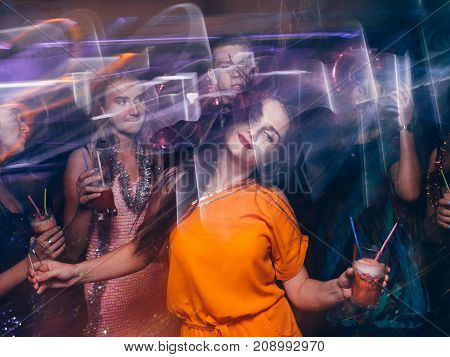 Disco party in night club in blurred motion. Happy friends dancing at Christmas celebration, active New Year company, modern youth life