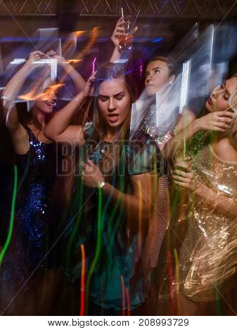 Active girl in night club in blurred motion. Stylish lady at Christmas discotheque, New Year company, modern youth life
