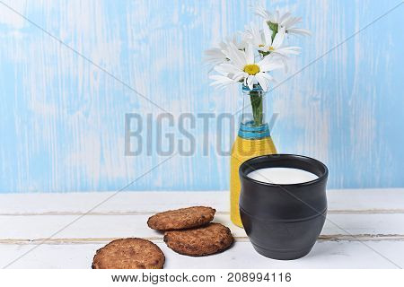 A bouquet of daisies and cookies with milk on the table
