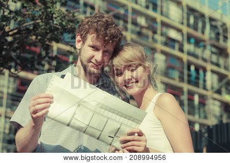Real estate and family concept - young couple on front of new big modern house with blueprint project dreaming about home