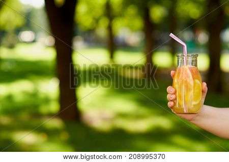 Healthy sweet citrus detox drink in hand on green blurred summer background. Fresh cold tea jar outdoors. Diet or healthy lifestyle, well being and weight loss concept