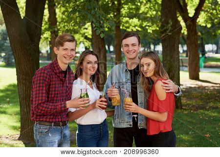 Group of happy young people enjoys detox cocktails and spend time together at summer. Friendship, youth lifestyle, vegetarian diet, fitness food on the go, successful weight loss concept