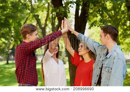 Happy young friends teamwork. Group of man amd woman with hands together doing give high five gesture. Friendship forever, togetherness, youth team , success concept