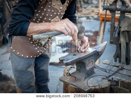 Blacksmith working the metal on Anvil in the foreground