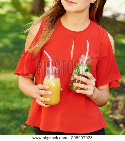 Healthy lifestyle. Unrecognizable young woman with fruit detox smoothie in summer, on green nature background. Diet, well being and weight loss concept