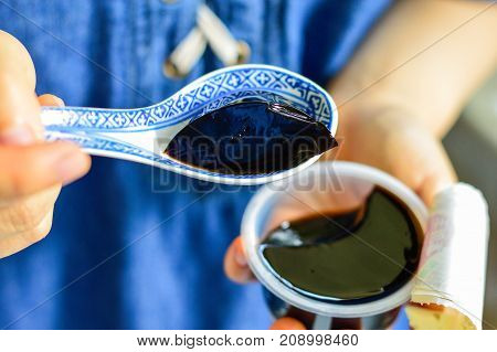 Hands Holding Black Guiling Gao, A Chinese Herb Jelly Dessert.