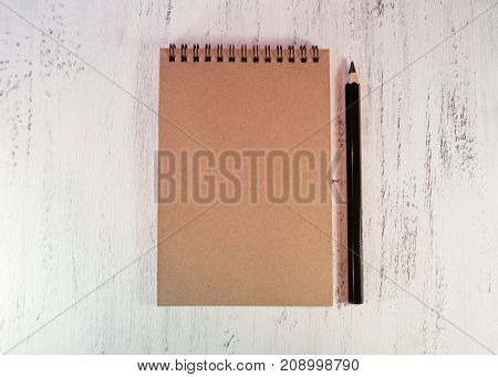 Notepad For Notes Or For Sketches On A Wooden Table. Near The Black Pencil.