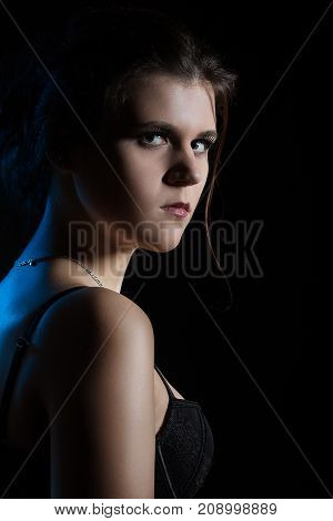 beautiful sad young woman on black background looking over shoulder at camera