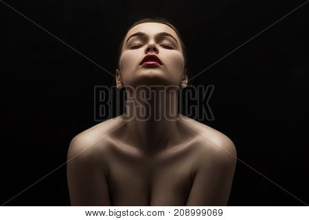 beautiful young naked woman posing sensually holding head up on black background