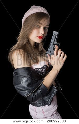 serious girl with gun on black background looking at camera
